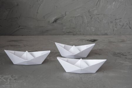 The concept of equality among white paper ships on gray background