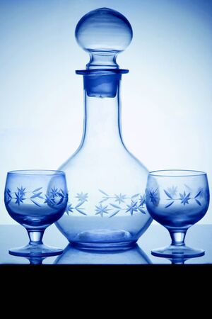 Empty crystal alcoholdecanter and two glasses for vodka standing on a glass table. Vertical side view, cold tone.