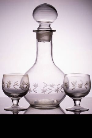 Empty crystal alcohol decanter and two glasses for vodka standing on a glass table. Vertical side view, black and white color