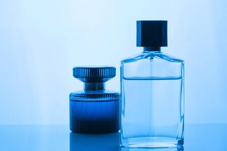 Women and man perfume bottle set on classic blue background with reflection. Aftershave, cologne. Selective focus