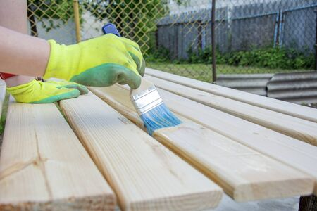 Woman Hand with a brush varnishes old wooden boards. Worker paint with brush a wood wall from boards in construction site.