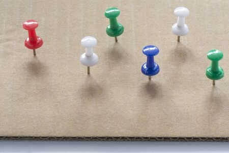 Multi colored Push Pins on White cardboard paper texture Background. Pushpins collection