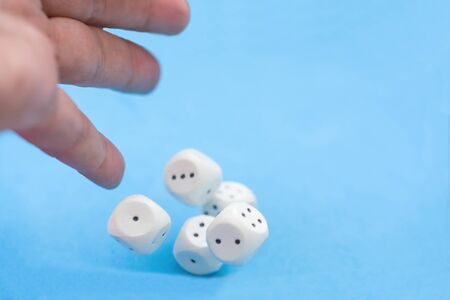 Man hand throwing five casino dices on blue background. Blurred, gaming moments in dynamic