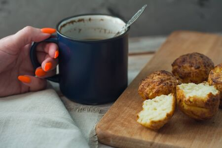 The girl drinks coffee from a large blue mug with muffins. Breakfast background Фото со стока - 149865519