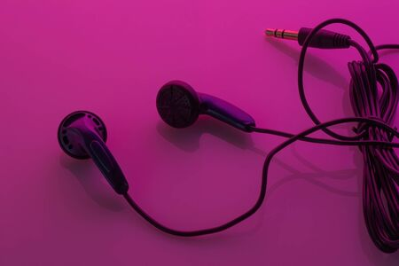 Black headphone wires on purple background with reflection. Accessory for portable gadgets, mobile phone, music player, laptop or tablet Фото со стока
