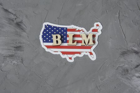 BLM word on a gray background with american flag. Fight against racism concept