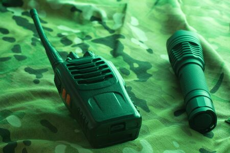 Equipment for trekking on camouflage background. Walkie-talkie and