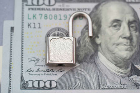 Opened security lock, open padlock on dollar bill background . Money protection concept. Banking security breach