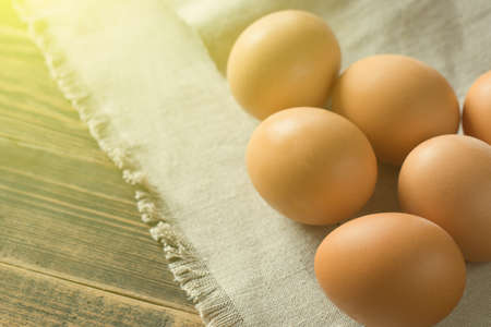 Chicken eggs on a vintage background with copyspace. Breakfast in the sun