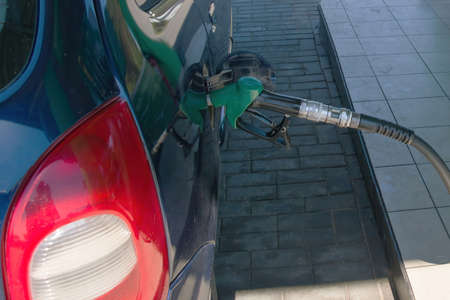 Filling gun into the hole of empty gasoline tank of car on diesel fueling. Filling station concept Фото со стока - 150655729