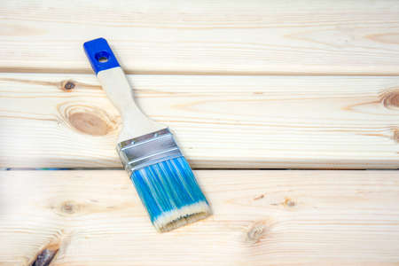 Brush on wooden boards background. Concept of repair, construction or House improvement diy