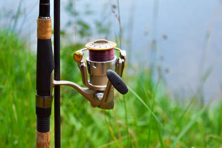 Feeder fishing rod with coil on the stand against the background of the river and grass. Feeder fishing in English style. The concept of rural getaway Фото со стока