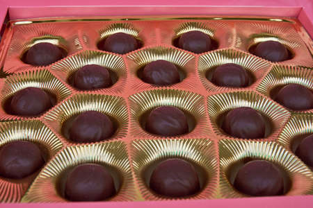 Chocolate candies in red box. Group of delicious chocolate pralines Фото со стока