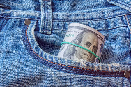 Roll of dollar banknote in worn jeans pocket. Saving money concept
