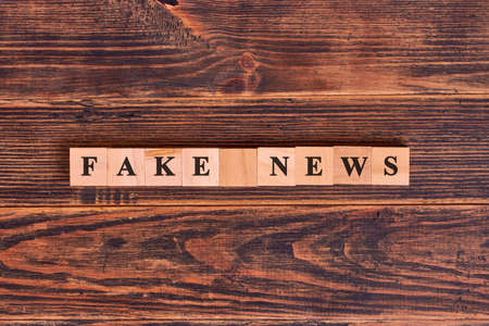 Fake news word written on wood block. Media technology and modern lifestyle concept