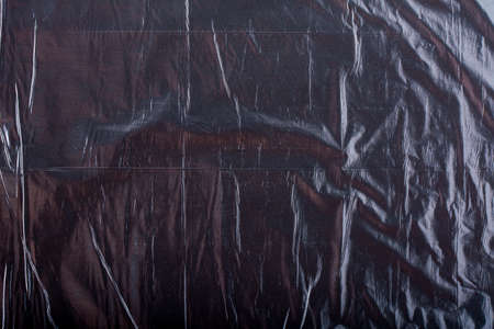 Texture of black crumpled garbage plastic bag. Abstract background for design