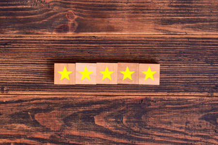Five star symbol on wooden blocks. Customer experience survey and satisfaction feedback concept