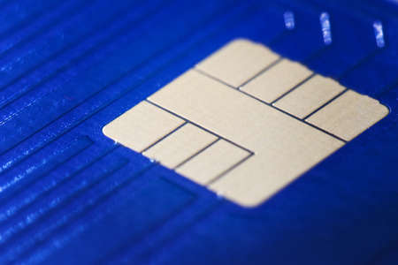 Closeup defocused view of blue plastic credit card EMV micro chip. Selective focus. Financial and Banking, Smart Payment Concept.