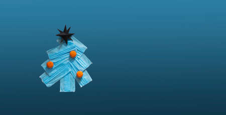 Banner Christmas tree made from face masks with orange tangerine decor on blue background. New year's eve 2021 in the context of the coronovirus pandemic, lockdown quarantine, shallow depth of field Stok Fotoğraf