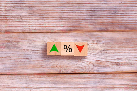 Wooden cube block with icon percentage symbol and arrow up and down direction. Interest rate, financial, ranking and mortgage rates business concept.