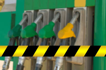 Gas station closed. Petrol pump not work. Black and yellow line of barrier tape forbids passage. For repairs, maintenance, fuel drain, strike. No petrol, crisis