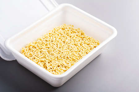 Instant Chinese noodle on gray background. Asian Fast food, junk food, unhealthy food. Rolton or Doshirak