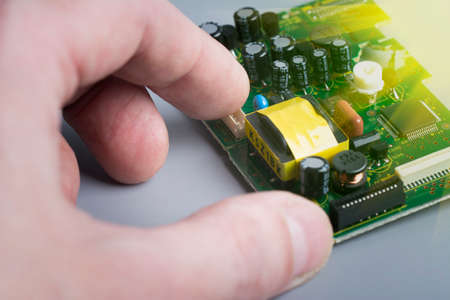 Technician hold pcb in hand. Electronic components on printes circuit board. Technical support and repair. Electronics Manufacturing Services