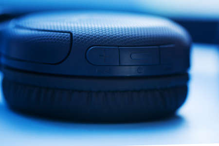 Wireless Headphones with buttons on blue background. Closeup view. Music concept. Shallow depth of field image