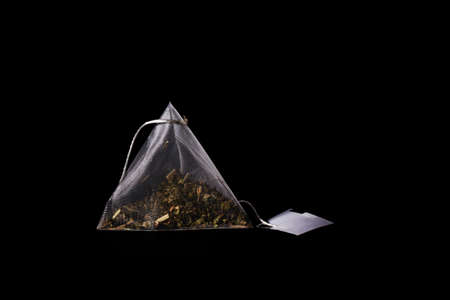Floral tea bag with white label isolated on black background. Tea pyramid close up