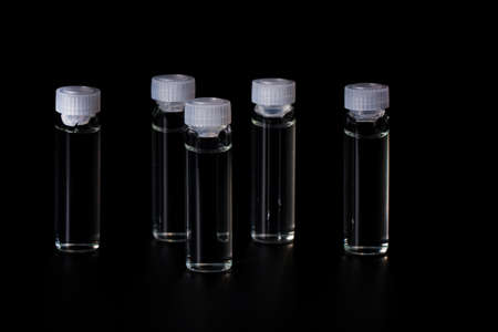 Cosmetic bottles with natural medicine, essential oil on black background. Transparent vials with hyaluronic acid