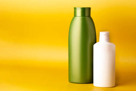 Plastic green and white cosmetic bottles without label on yellow background. Shampoo or hair lotion. Body care and beauty products concept. Фото со стока