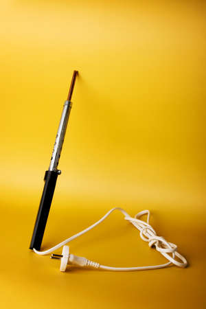 Soldering iron with black plastic handle and white cord on yellow background. Tool for DIY soldering and repairing electronic device boards. Vertical view. Фото со стока
