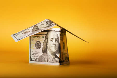 House Made from 100 dollar bills Cash Money on Yellow Background. Property investment and house mortgage financial concept. Фото со стока