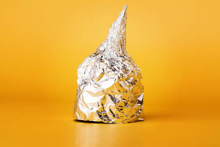 Hat made of aluminum foil on yellow background. Used by those who are afraid of 5G radiation or aliens. Symbol for conspiracy theory. Tin foil cap paranoia