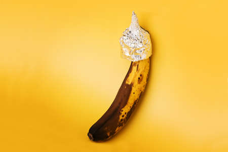 Overripe banana in aluminum foil hat on yellow background. Symbol for conspiracy theory. Фото со стока