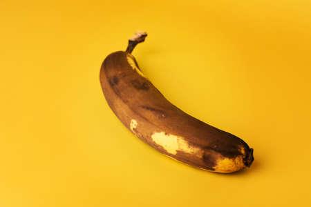 Overripe Banana on yellow background. Very ripe brown spotted organic banana.