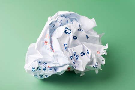 Crumpled paper calendar sheet on green background. Фото со стока