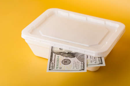 White plastic box with 100 dollar banknote on yellow background.
