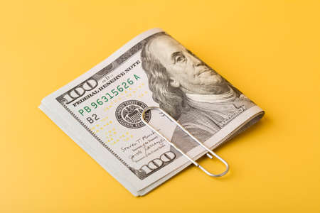 The 100 dollar bills are folded in half and held together with a paper clip on yellow background.