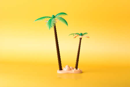 Tropical coconut palm toy on yellow background.