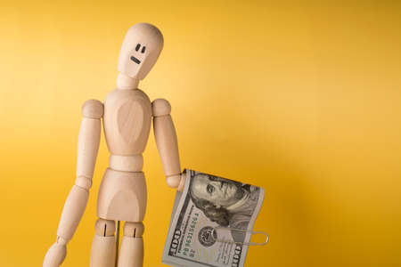 Figure of wooden man with sad expression holds 100 dollar bills with paper clip on yellow background. Фото со стока