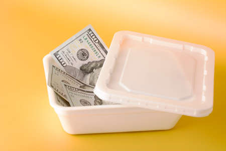 White plastic box with 100 dollar bills on yellow background. Business investment concept.