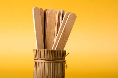 Wooden ice cream sticks in bamboo vase on yellow background. Minimal business teamwork concept