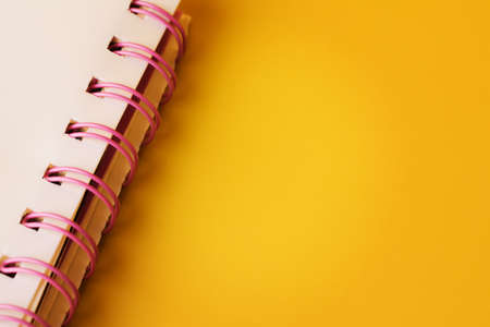 Blank spiral notepad on yellow background. Sketchbook for note
