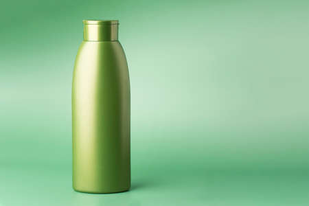 Green cosmetic bottle isolated on mint green background with copyspace. Container for cosmetics product. Skincare and beauty concept