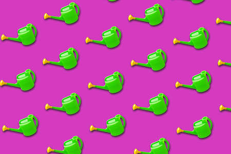 Green plastic watering can on purple background. Minimal creative bold colored garden pattern. Spring or summer, growing concept