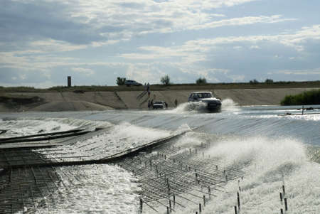 reclaiming: On a dam partitioned off the river Big Irgiz and the filled in water the car moves. Stock Photo