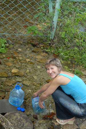 capacities: The harmonous nice woman types water in plastic capacities from a spring.