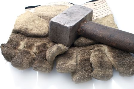disrupt: Dirty leather gloves and sledgehammer,isolated on white Stock Photo