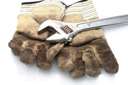 Dirty leather gloves and monkey wrench,isolated on white photo